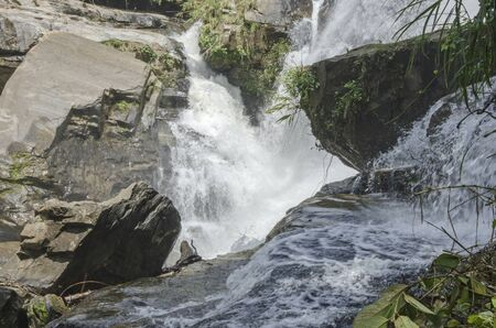 Strong stream of waterfall into deep abyss Imagens