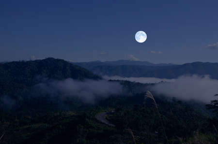 Beautiful white full moon over the mountains in the winter