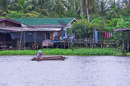 Nakornpathom, Thailand. September 29, 2020  People row a boat pass old house and palm garden Editorial