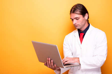 Male doctor holding laptop in his arms