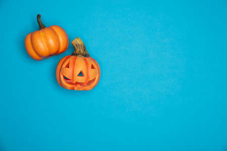 Halloween sculpted pumpkin funny and cute faces. Flat lay against blue background
