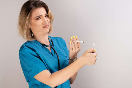 Female doctor with stethoscope, cigarette and lighter displaying negative attitude on smoking Banco de Imagens