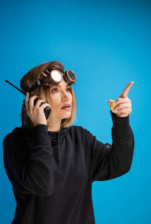 Portrait of dark blonde girl with steam punk glasses using a walkie talkie communication device and pointing with finger Foto de archivo