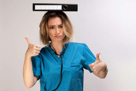 Crazy female doctor balancing documents on her head displaying thumbs up Banco de Imagens