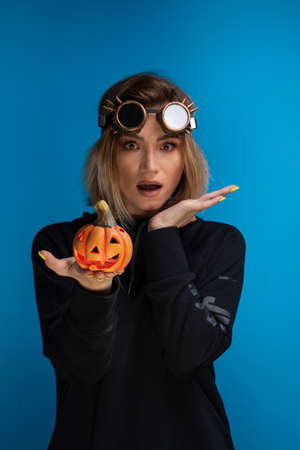 Woman with steam punk glasses and black hoodie holding carved Halloween pumpkin wondering and making funny faces Foto de archivo