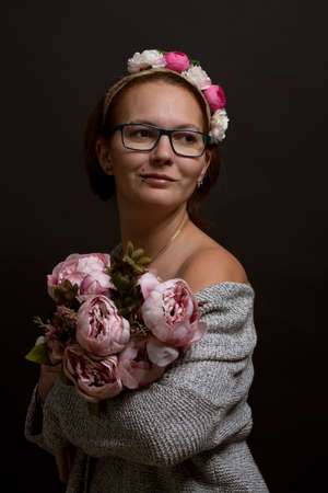 Portrait of young woman wearing eye glasses, holding flowers Stockfoto