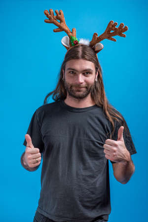 Male wearing raindeer hair band showing thumbs up with both hands