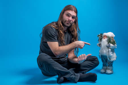 Long-haired male pointing to a toy Santa while sitting down
