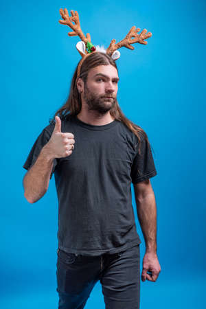 Male wearing raindeer hair band with straight face displaying thumbs up sign Stock Photo