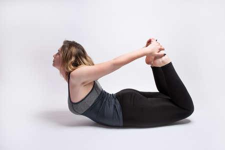 Blonde woman performing Bow Pose Dhanurasana yoga pose