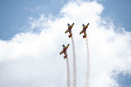 Three airplanes in the sky within clouds performing acrobatics during an air show at Kogalniceanu romanian airport