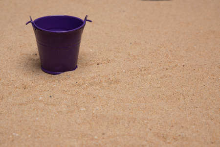 Isolated purple toy bucket on very fine sand Imagens