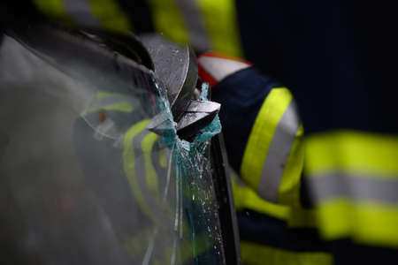 Car wrecked in accident receiving assistance from intervention team in order to remove the victim by tearing the glass with a claw tool Фото со стока