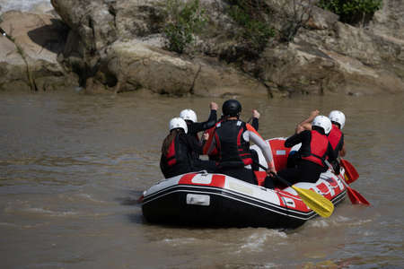 Team members rowing in the rafting boat down the murky river during summer time