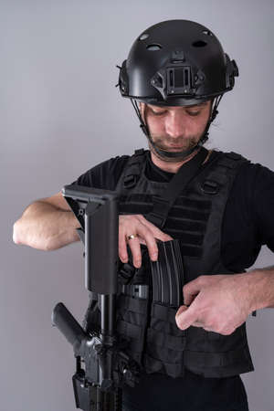 Close up of male equipped for airsoft adding an extra magazine to his vest while looking down.