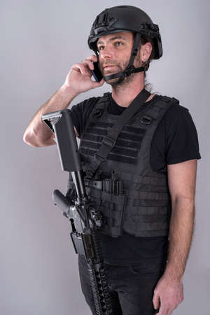 Man equipped for airsoft with helmet and protective vest is confirming the negociation strategy on the phone while standing with his weapon displayed Stock Photo