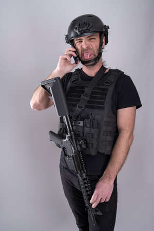 Standing man equipped for airsoft with helmet and protective vest is sticking his tongue out to the camera making a grimace while confirming the negociation strategy over the phone. Stock Photo