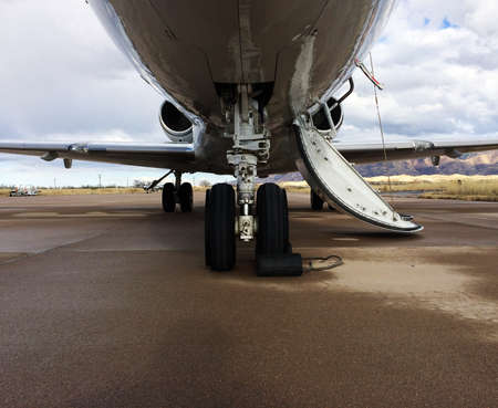 undercarriage: This photo consists of a landing gear of a Private Jet which is taken from the front of the airplane. Also contains a good view of the wings and the jet engines. With its door open, it urges you too come on board!!