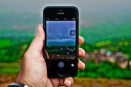 This a photo of a phone taking a photo of a scenery which was located at quite some height above sea level during the monsoon season in India. Photo taken from a Digital SLR.