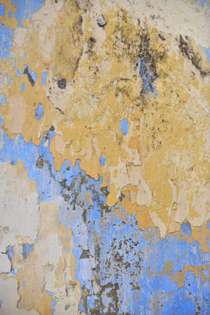 Beautiful colors layers of an outdoor plaster wall showing several times of wall repairing. Each color showing a new layer had been added to hide the old one below from time to time.
