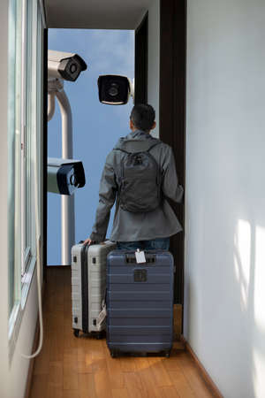 A male traveler is looking at the CCTV surveillance system and thinking about his privacy while staying this modern small hotel. He is about to check in with suitcases and backpacks in the morning. Banque d'images - 119879403
