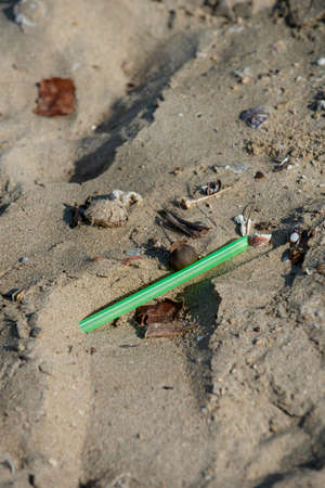 Green straw found left on the beach. A starting point of the environment problem. 写真素材
