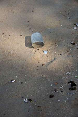 Plastic bottle found half left on the beach in the morning. A starting point of the environment problem.