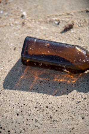 An empty brown clear bottle with cap left on the beach. A starting point of the environment problem. 写真素材 - 119881097