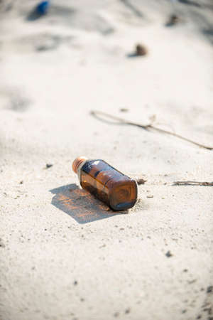 An empty brown clear bottle with cap left on the beach. A starting point of the environment problem.
