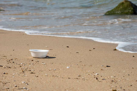 White foam cup found left on the beach. A starting point of the environment problem. 写真素材 - 119881103