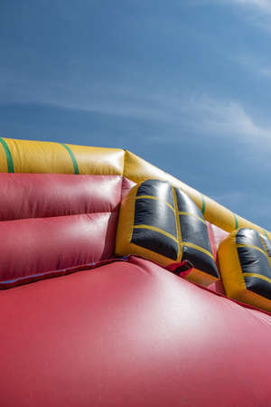 A giant colorful inflatable slider with joyful kids running up and down the slider in the fun park with happiness.