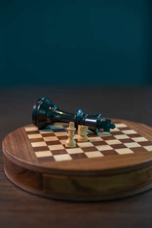 An abstract chess game with a little white king and knight checkmates a big black king on the wooden chess board.