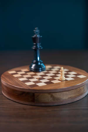 An abstract chess game with a little white king playing against a big black king on the wooden chess board.