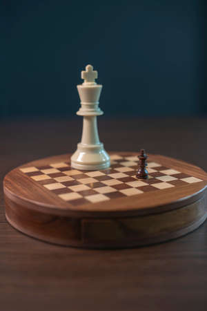 An abstract chess game with a little black king playing against a big white king on the wooden chess board. 写真素材