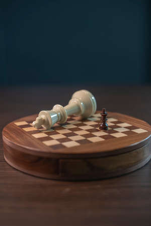 An abstract chess game with a little black king checkmates a big white king on the wooden chess board.