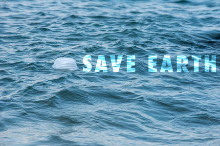 Save Earth awareness on Earth day and every day. A white empty form found left floating on the sea shore. A major problem of a Global issue. 写真素材