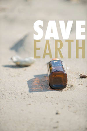 Save Earth awareness on the Earth day. Empty brown clear bottle with cap left on the beach. A starting point of the environment problem.