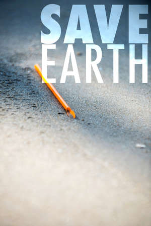 Save Earth awareness on Earth day and every day. Orange straw found left trashed on the beach. A starting point of the environment problem.