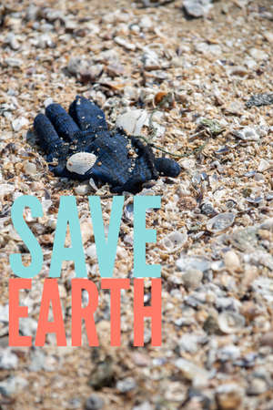 Save Earth awareness on the Earth day. A deep blue winter yarn glove found trashed on the beach surrounded with sea shells. 写真素材 - 120537715