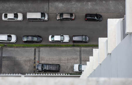 Top view from a high floor of a high rise building seeing cars parking on a small street. 写真素材