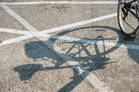 Old vintage bicycle parking near a walk way in the morning. Its shadow casts on the street with an interesting lines.