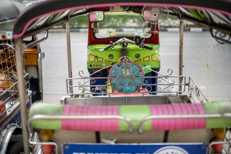Well known and famous local taxi in Thailand, Tuk-Tuk, parking nearby tourist place, waiting for passengers asking for a ride. Image showing lots of details of colourful equipments and elements.