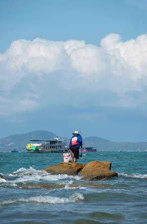 Guy has a quiet moment by himself, fishing on the rock near the Pattaya beach, Thailand.