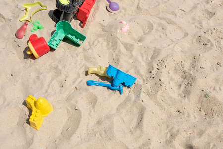 Colourful plastic toys with various shapes and kinds left unattended on a sand box in a resort, waiting for kids to come and enjoy them in a morning.