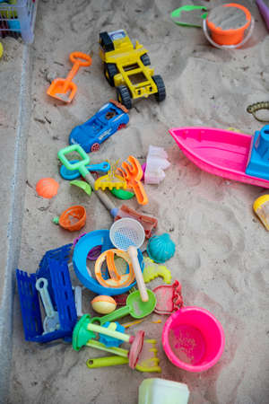 Colourful plastic toys with various shapes and kinds left unattended on a sand box in a resort, waiting for kids to come and enjoy them in a morning. 写真素材 - 122574520