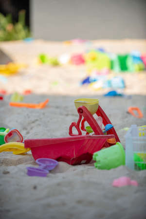 Colourful plastic toys with various shapes and kinds left unattended on a sand beach, waiting for kids to come and enjoy them. 写真素材