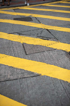 Yellow lines painted on the road, showing traffic rules guide for drivers and pedestrians to follow the laws.