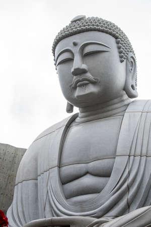 Closeup of sitting & peaceful giant Buddha statue inside Hill of the Buddha, Buddhist shrine at Makomanai Takino Cemetery, Sapporo, Hokkaido, Japan. Designed by Tadao, a Japanese modernist architect.