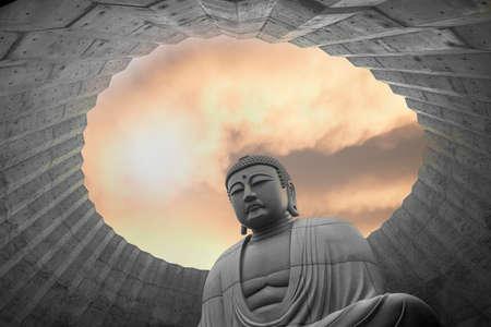 Superimposed or double exposures of sitting giant & peaceful Buddha statue inside Hill of the Buddha with a beautiful orange sun set. A Buddhist shrine at Makomanai Takino Cemetery, Sapporo, Hokkaido.