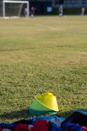 Colourful bibs left on a football pitch, ready for the next training session to come. Colourful cones for sport practice on a football pitch in the summer evening at high school. Фото со стока